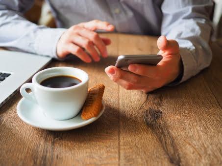 コーヒーを机の上に置いてスマートフォンを操作している男性の画像